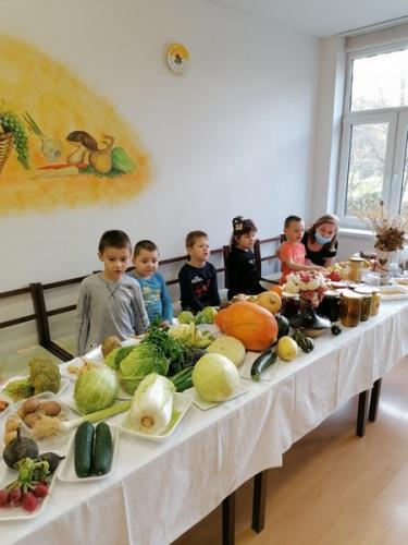 deti za stolom plným ovocia a zelniny